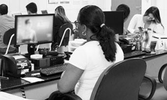 Professora orientando alunos no computador